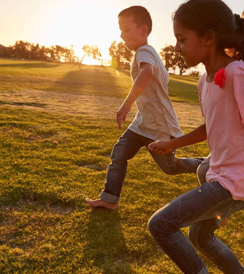 four-children-running-barefoot-in-a-park-PSCW4NU