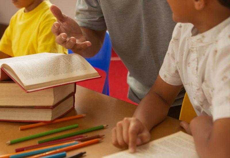 male-teacher-teaching-a-cute-mixed-race-schoolboy--ZWYTHEM